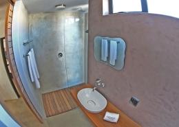 Badezimmer im Windtown Lagoon Hotel mit großer Dusche, die ebenerdig ist.