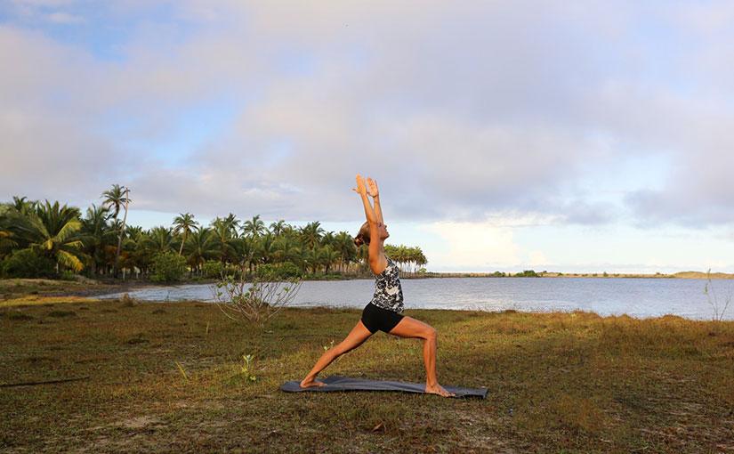 Die Kriegerposition beim Yoga an der Lagune in Kalpitiya, Sri Lanka.