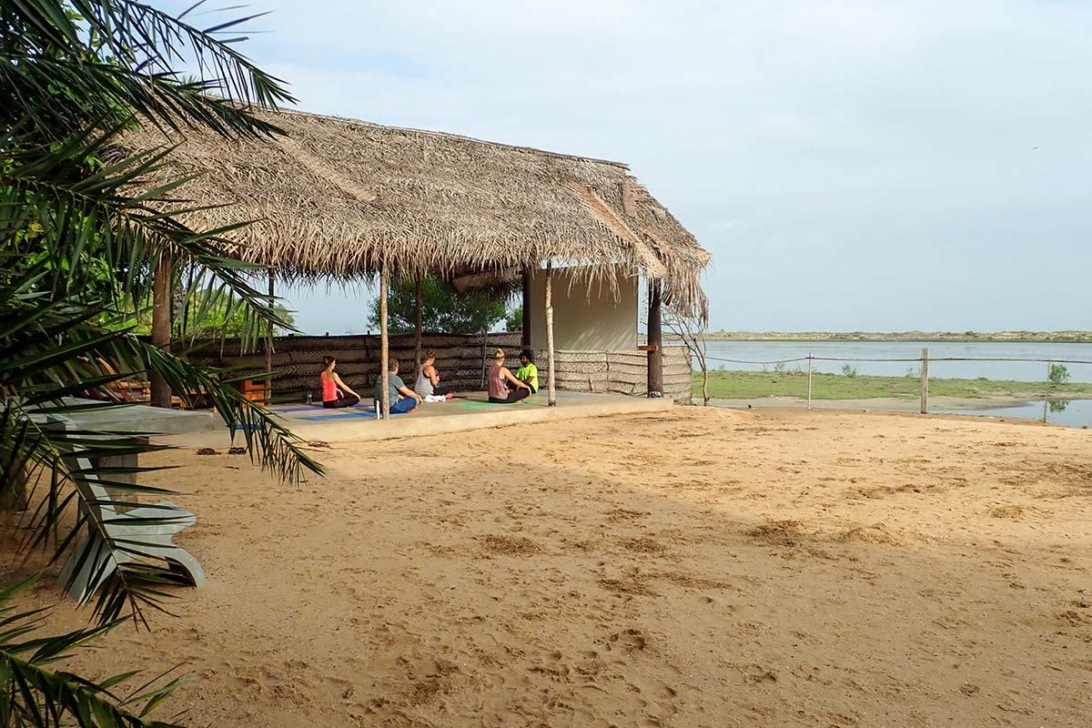Unter einem Palmendach wird bei KiteWorldWide in Kalpitiya auf Sri Lanka Yoga unterrichtet.
